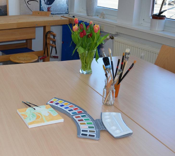 Malkasten und gemaltes Bild auf Tisch